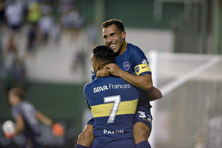 Boca Juniors' forward Carlos Tevez (top) celebrates after scoring a goal against Banfield during their Argentina First Division Superliga football match at  Florencio Sola stadium, in Banfield city, near Buenos Aires, on February 18, 2018. / AFP PHOTO / Pablo Aharonian