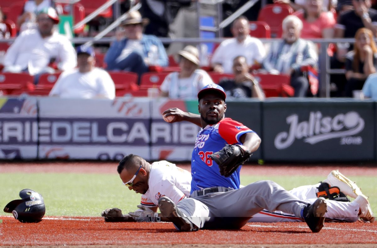 Rene Reyes (L) of Venezuela's Caribes de Anzoategui tags out at second base David Richardson (R) of Puerto Rico's Criollos de Caguas during the Caribbean Baseball Series at the Charros Jalisco stadium in Guadalajara, Jalisco state, Mexico, on February 5, 2018. / AFP PHOTO / ULISES RUIZ