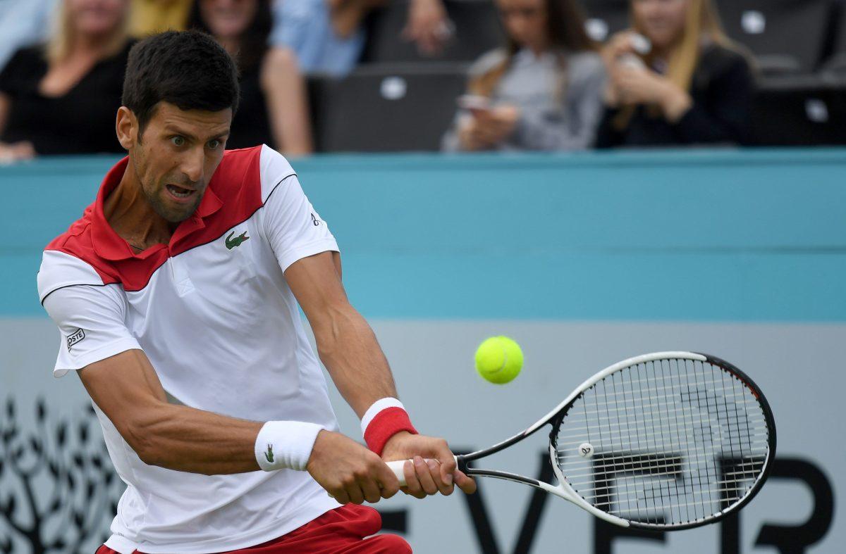 EPA7921. LONDRES (REINO UNIDO), 19/06/2018.- El tenista serbio Novak Djokovic devuelve la bola al australiano John Millman, durante el partido de la primera ronda del torneo de Queen's que se disputa en Londres, Reino Unido, el 19 de junio del 2018. EFE/Neil Hall